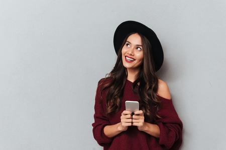 Encantadora joven con sombrero negro y suéter de punto con smartphone, mirando a un lado, aislado sobre fondo gris