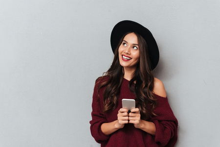 Charming young woman in black hat and knitted sweater holding smartphone, looking aside, isolated on gray background