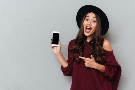 Happy exited brunette girl in black hat pointing with finger on blank mobile screen, isolated on gray background