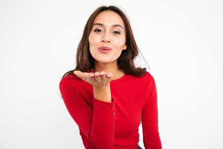 Portrait of a lovely pretty asian woman sending air kiss while standing and looking at camera isolated over white background