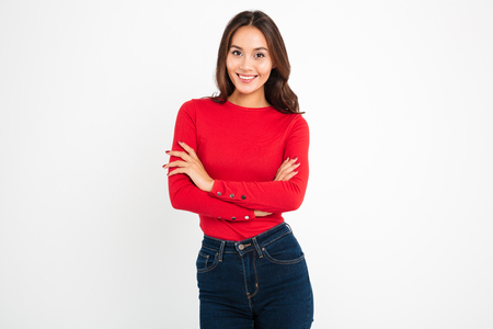 Photo of beautiful young happy woman standing with arms crossed isolated over white wall background. Looking camera.