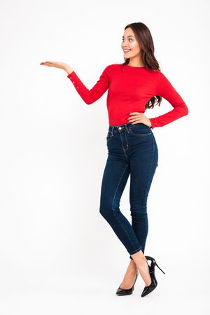 Full-lenght picture of young happy woman standing isolated over white wall background. Looking aside holding copyspace in hand.