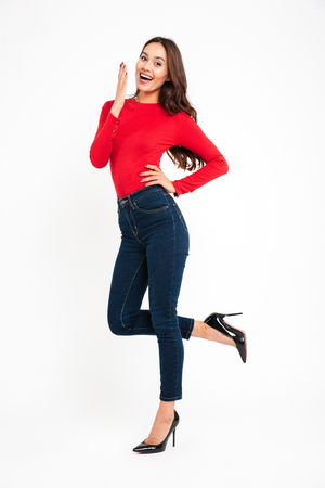 Full length portrait of a young beautiful asian woman posing while standing and looking at camera isolated over white background Фото со стока