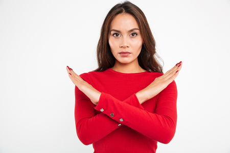 Portrait of a concentrated serious asian woman holding her hands crossed and looking at camera isolated over white background Standard-Bild