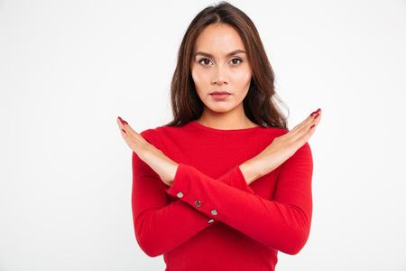 Retrato de una mujer asiática seria concentrada con las manos cruzadas y mirando a la cámara aislada sobre fondo blanco. Foto de archivo