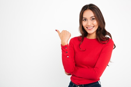 Photo of young cheerful woman standing isolated over white wall background. Looking camera pointing to copyspace.
