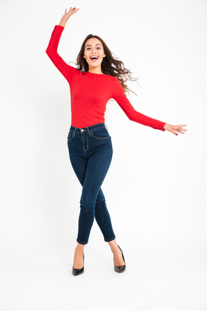Full-lenght image of young emotional cheerful woman posing isolated over white wall background. Looking camera.