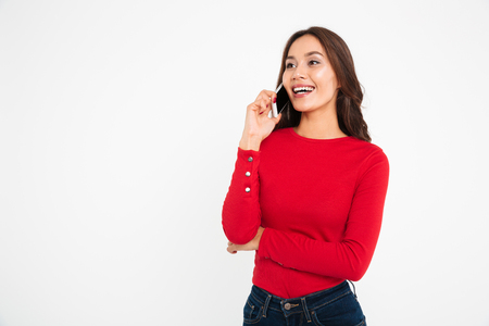 Portrait of a young smiling asian woman talking on mobile phone while standing and looking away isolated over white background