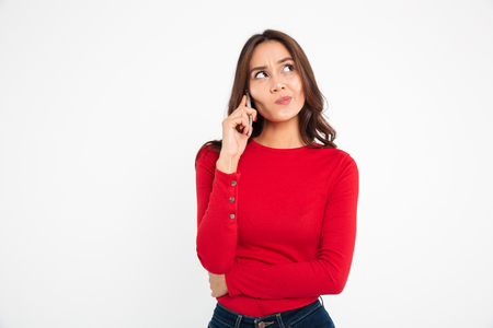 Portrait of a doubtful frustrated asian woman talking on mobile phone while standing and looking away isolated over white background Banco de Imagens