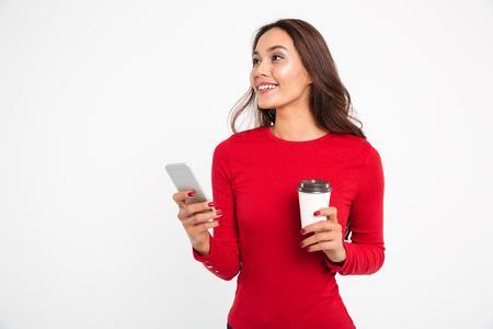 Retrato de una mujer asiática sonriente feliz que sostiene el teléfono móvil mientras que bebe el café y mira para arriba aislado sobre el fondo blanco Foto de archivo