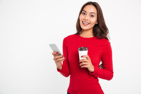 Portrait of a happy young asian woman holding mobile phone while drinking coffee isolated over white background