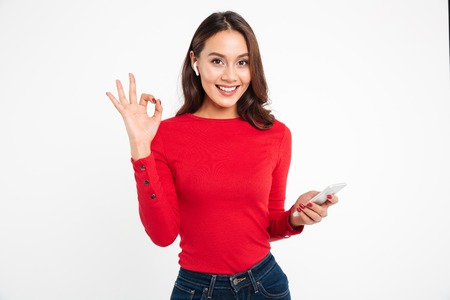 Portrait of a smiling happy asian woman in earphones holding mobile phone while standing and showing ok gesture isolated over white background