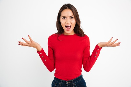 Portrait of an angry confused asian woman screaming and looking at camera isolated over white background