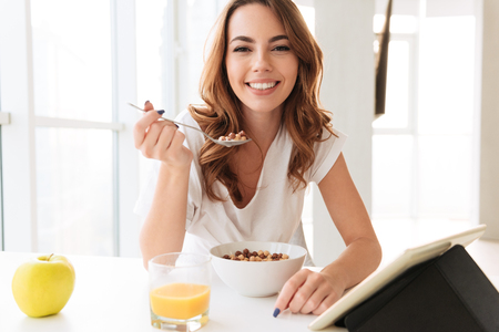 Photo of amazing young lady sitting at the kitchen near window. Looking camera eating corn flakes using tablet computer.