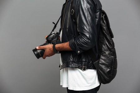 Cropped photo of stylish african man with backpack holding photo camera, isolated on gray background 版權商用圖片