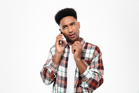 Portrait of a pensive young african man dressed in plaid shirt holding hand at his chin while talking on mobile phone isolated over white background