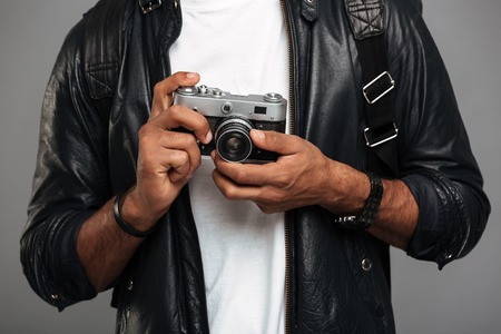 Close up of a young african male photographer in leather jacket holding retro camera isolated over gray background