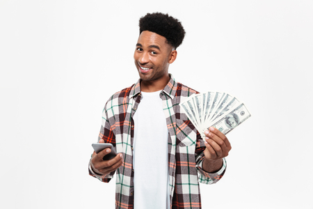 Portrait of a cheery young african man dressed in plaid shirt holding mobile phone and bunch of money banknotes isolated over white background