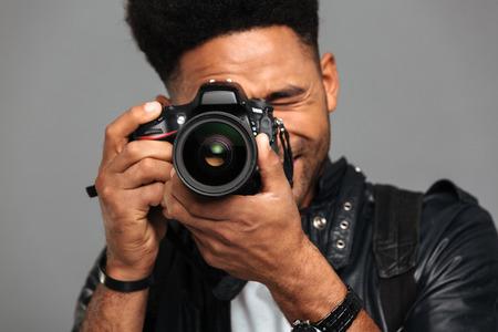 회색 배경에 고립 된 디지털 카메라에 집중된 afro 미국 남자 복용 사진의 근접 사진