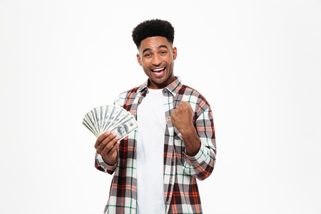 Portrait of a happy african man holding bunch of money banknotes and celebrating success isolated over white background Stock Photo