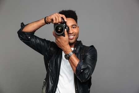 Portrait of a smiling afro american guy in leather jacket taking a photo with retro camera isolated over gray background