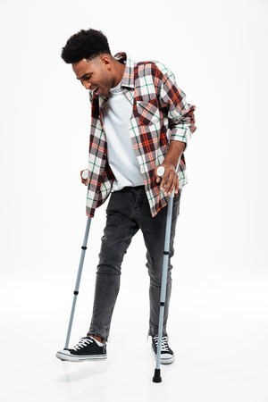 Full length portrait of a young afro american man walking on crutches isolated over white background