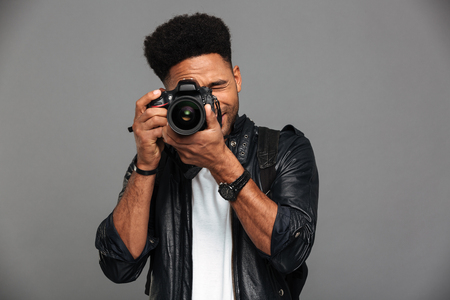 Handsome african guy with stylish haircut taking photo on digital camera, isolated on gray background Reklamní fotografie
