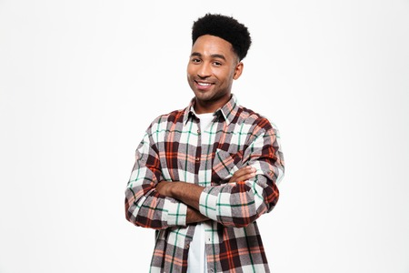 Portrait of a smiling african man dressed in plaid shirt standing with arms folded and looking at camera isolated over white background Stock fotó