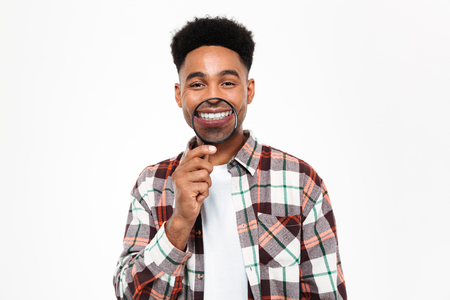 Portrait of a funny young african man playing with magnifying glass isolated over white background Stock Photo