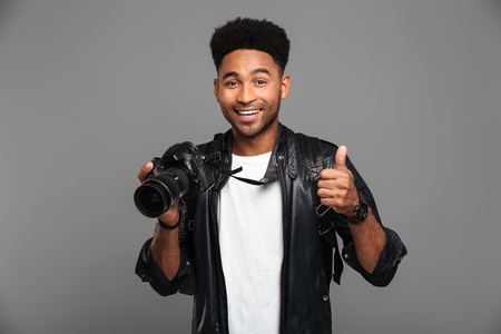Young smiling afro american man holding photocamera and showing thumb up gesture, looking at camera, isolated on gray background