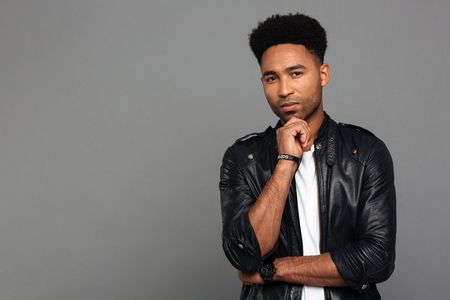 Portrait of a young contemplative afro american man in leather jacket standing with hand on chin and looking at camera isolated over gray background