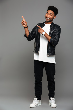 Full length portrait of cheerful handsome african man in stylish wear pointing with two fingers, looking at camera, isolated on gray background