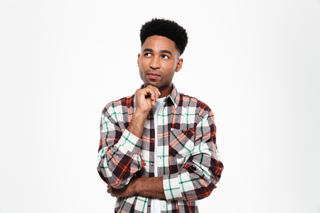 Portrait of a pensive young african man dressed in plaid shirt looking away at copy space isolated over white background Фото со стока