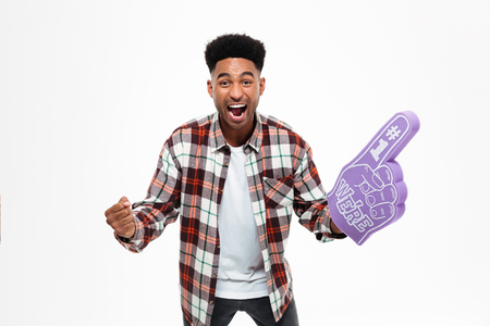 Portrait of a cheerful excited african man with a foam finger shouting and looking at camera isolated over white background Stock fotó