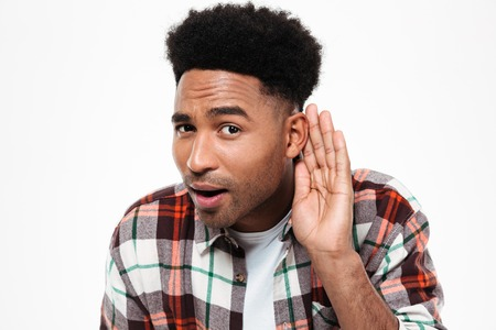 Close up portrait of a curious afro american man trying to hear something while keeping hand at his ear isolated over white background