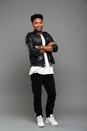 Full length photo of young cheerful african boy in leather jacket standing with crossed hands, looking at camera, isolated on gray background