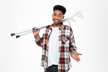 Full length portrait of a happy smiling young afro american man holding crutches and looking at camera isolated over white background