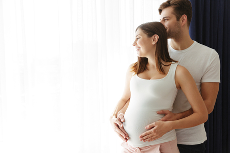 Picture of happy man hug his lovely pregnant wife indoors at home. Looking at window.
