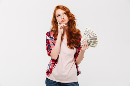 Image of thinking young redhead lady standing isolated over white wall background looking aside while holding money. Stock Photo
