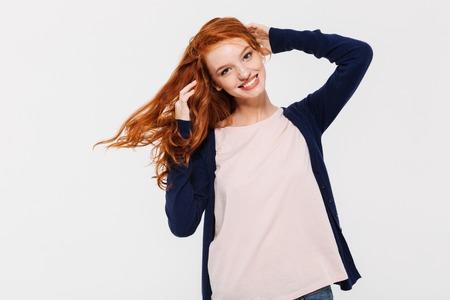 白い壁の背景の上に孤立して立っているかわいい若い赤毛の女性の笑顔の画像。カメラを探してる 写真素材