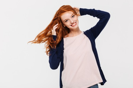 Image of smiling pretty young redhead lady standing isolated over white wall background. Looking camera. Stock fotó