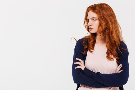 Photo of angry pretty young redhead lady standing isolated over white wall background with arms crossed. Looking aside. Фото со стока