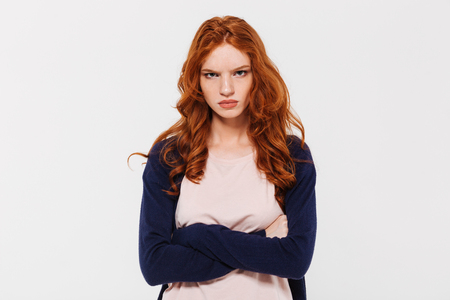 Image of angry pretty young redhead lady standing isolated over white wall background with arms crossed. Looking camera.