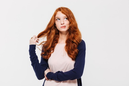 Picture of thinking cute young redhead lady standing isolated over white wall background. Looking aside. Stock fotó
