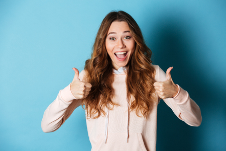 Image of cute happy lady standing isolated over blue wall background. Looking camera showing thumbs up..