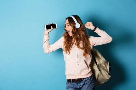 Portrait of a joyful attractive girl student with backpack listening to music with headphones while showing blank screen mobile phone and dancing isolated over blue background