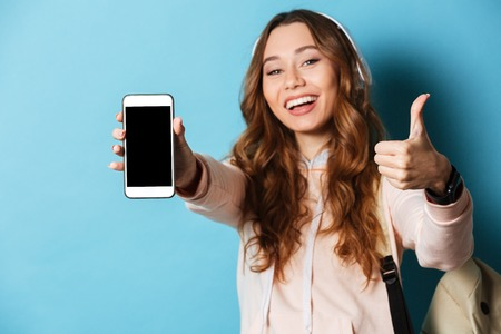 Portrait of a cheerful smiling girl student with backpack listening to music with headphones while showing blank screen mobile phone and giving thumbs up isolated over blue background Stock Photo
