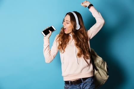 Portret van een vrolijke gelukkige studente die met rugzak aan muziek met hoofdtelefoons luisteren terwijl het tonen van het lege scherm mobiele telefoon en dansen geïsoleerd over blauwe achtergrond