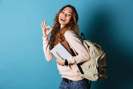 Portrait of a happy friendly girl student with backpack holding books and showing ok gesture isolated over blue background