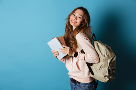 Retrato de una estudiante alegre sonriente con mochila sosteniendo libros y mirando a la cámara aislada sobre fondo azul.